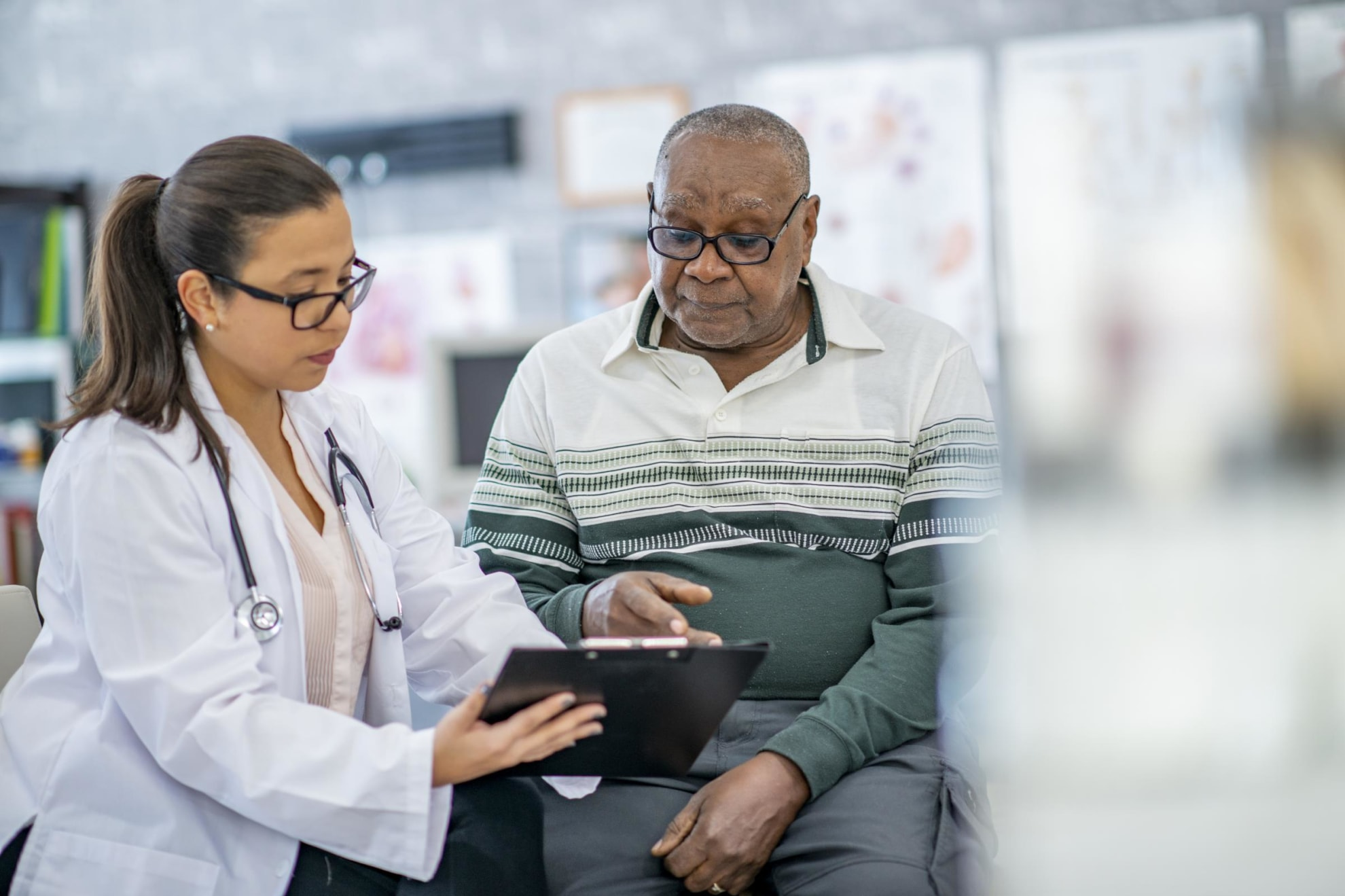A senior black man is sitting in his doctor's office and listening as the doctor shows him something on her clipboard.