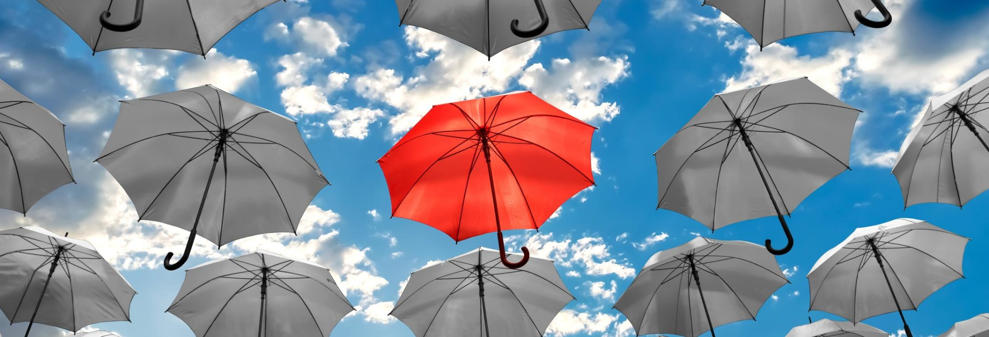 One red umbrella surrounded by white umbrellas floating in the sky