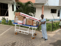 Dr. Ivan Rukundo transporting IR equipment to the procedure area.