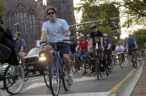 Group of cyclists riding down a New Haven street.