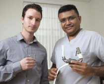 One of Pramod Bonde's recent inventions is a replacement for the left ventricular assist device, which he holds in his hands and must be implanted in the patient's chest. Medical student Brian Letzen, holds the smaller device.