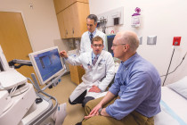 Peter Schulam (standing), chair of urology, and clinician Preston Sprenkle discuss a case with a patient
