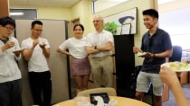 Kevin eating birthday cake with colleagues