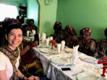 Nükte at a dining table with Cameroonian women.
