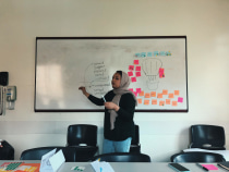 Uzma speaking in front of white board.
