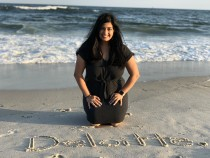 Lisa on Jones Beach with Deloitte written in the sand