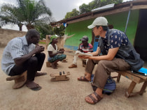 Harry and a translator sit with a couple in their yard