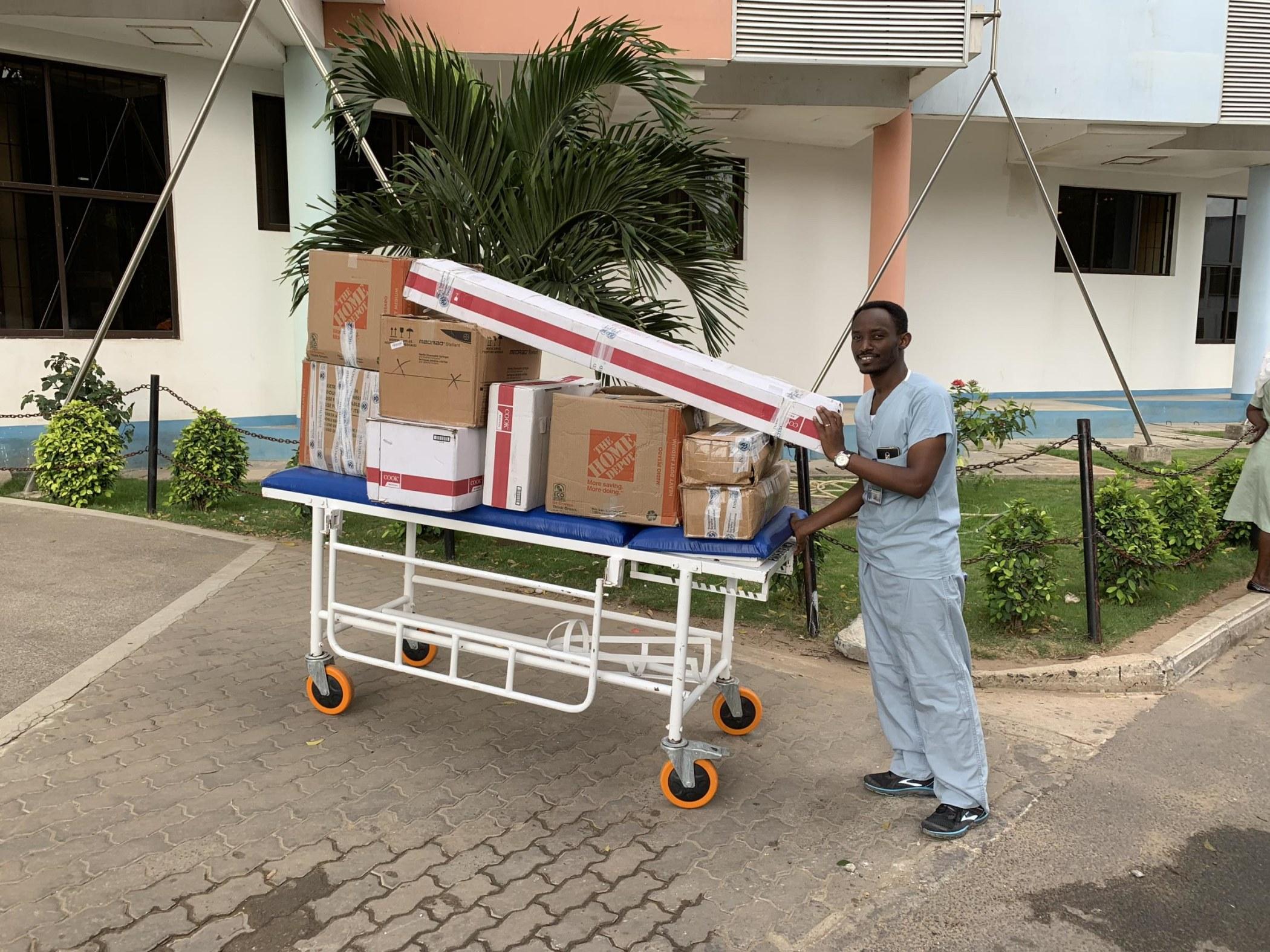 Dr. Ivan Rukundo transporting IR equipment to the procedure area.