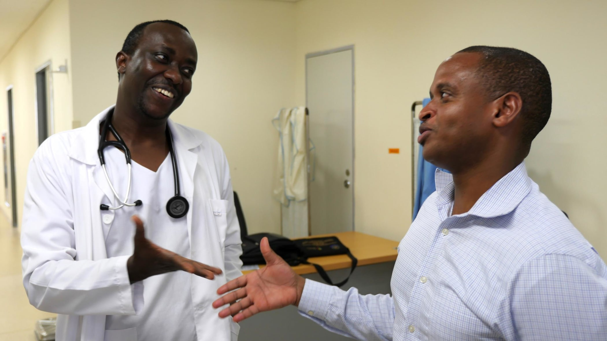 Dr. Pascal Ruggajo, Nephrologist and HOD Internal Medicine at MUHAS and Dr. Frank Minja from Yale shaking hands on future collaborations.