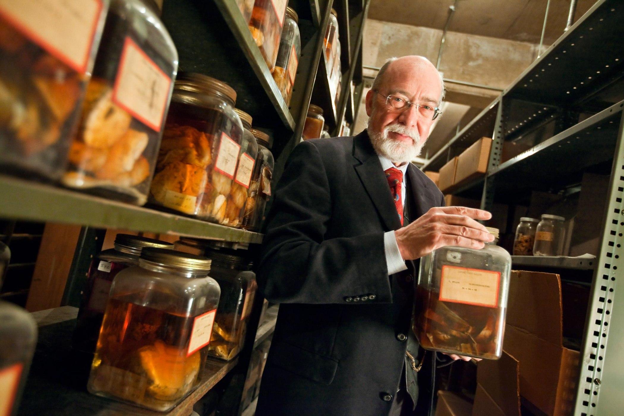 Dennis Spencer holds a brain specimen