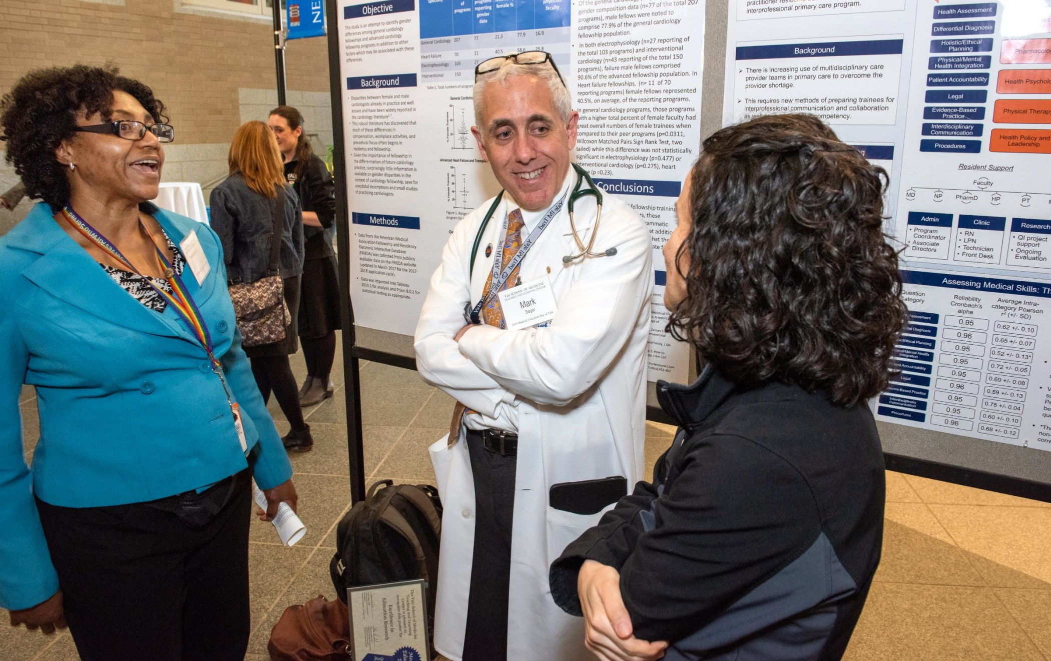Three Med Ed Day attendees discuss a poster