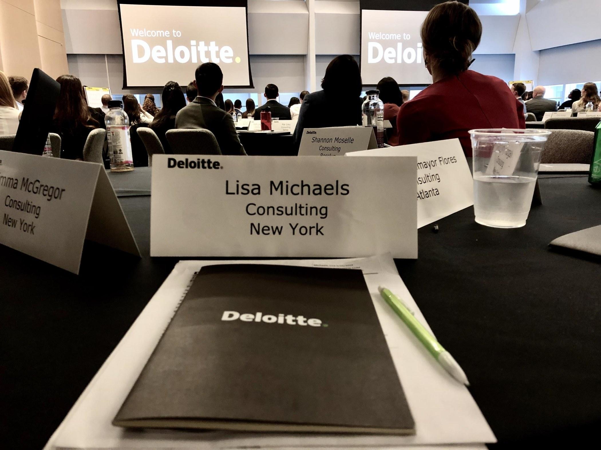 Lisa's name badge and Deloite folder