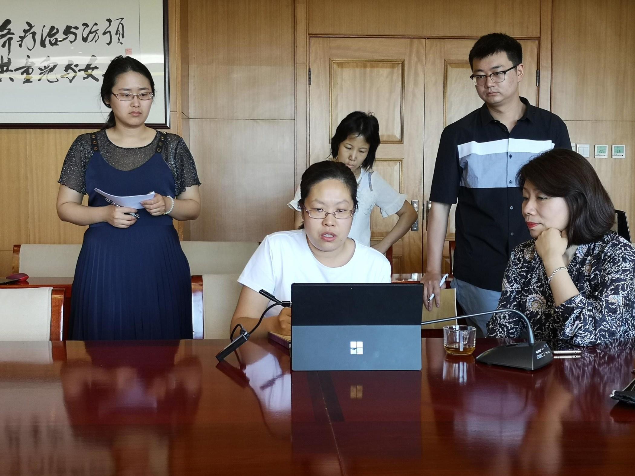 group gathered around a laptop