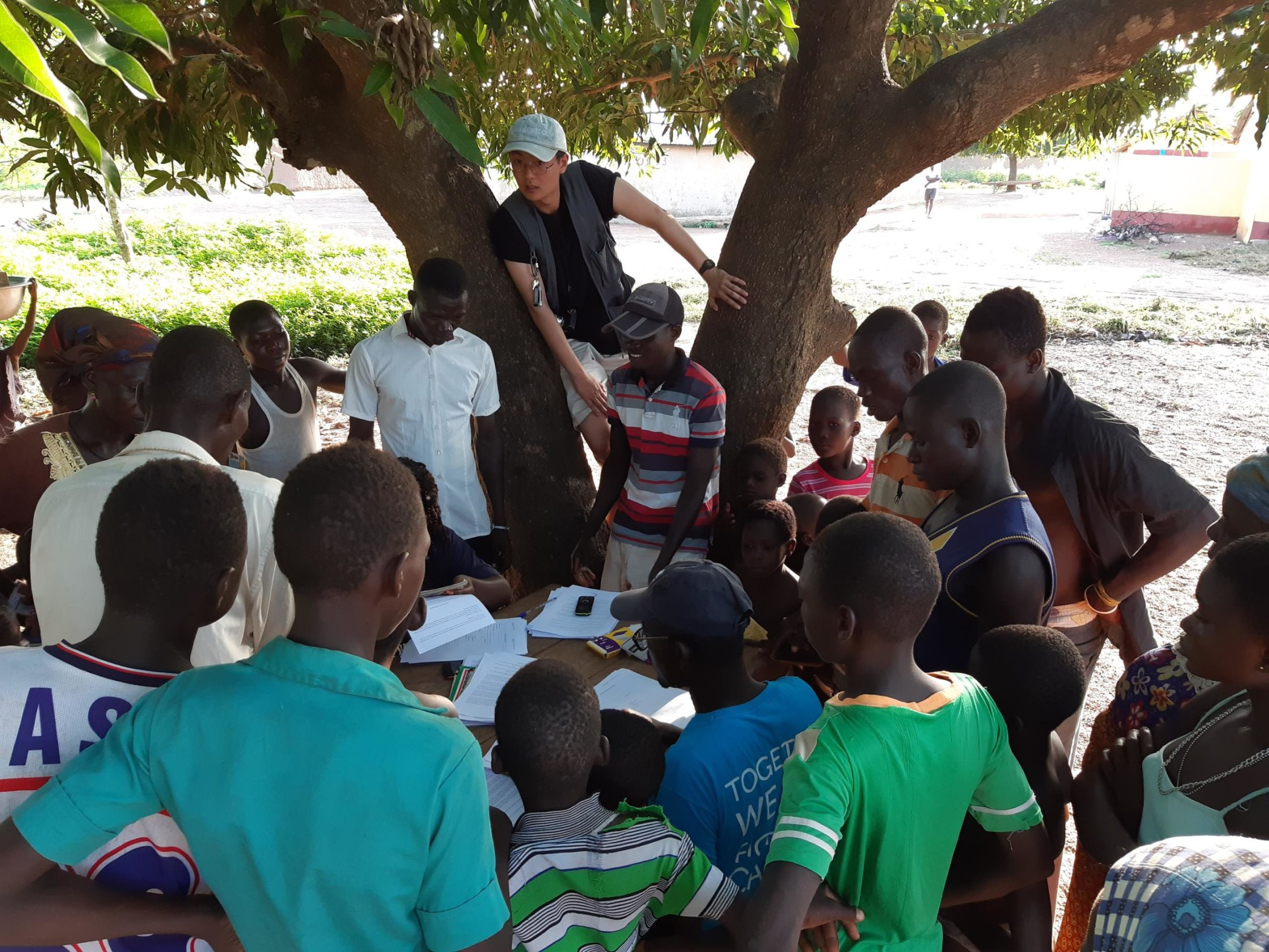 Harry sits in the crook of a tree with group of people while team collects data