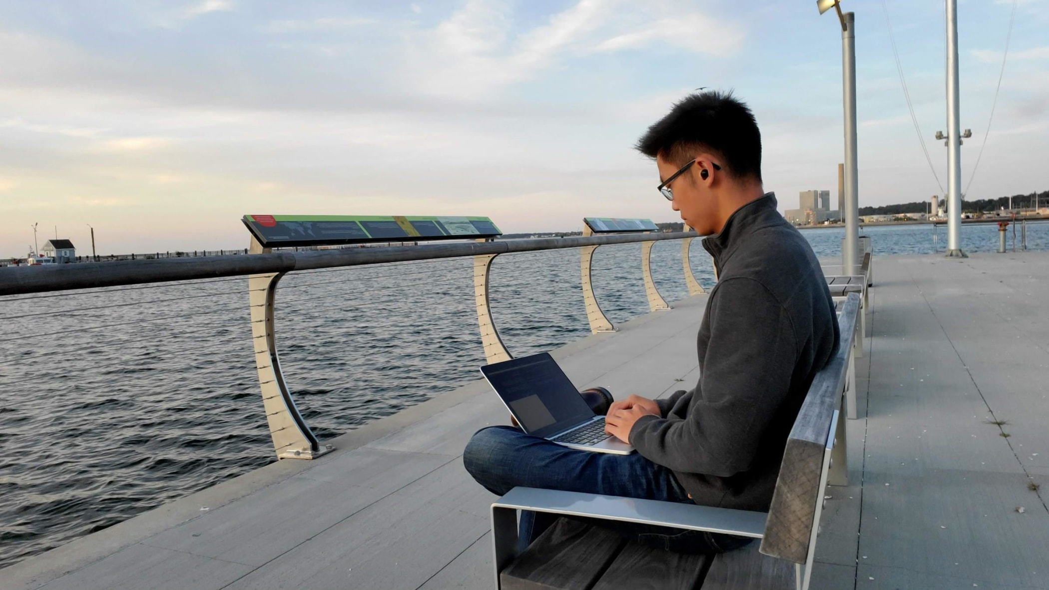 Kevin sitting on a bench with laptop by the water