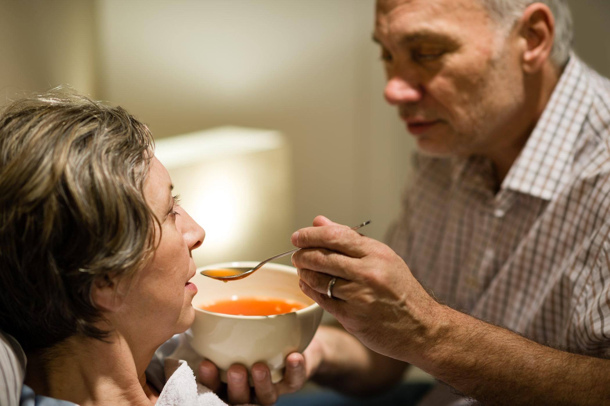 Man feeding his wife warm soup
