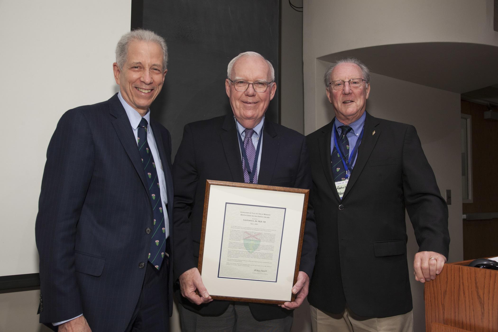 Leo Cooney, M.D. '69, received the Distinguished Alumni Service Award from Dean Robert Alpern and AYAM President Harold Mancusi-Ungaro, M.D. '73