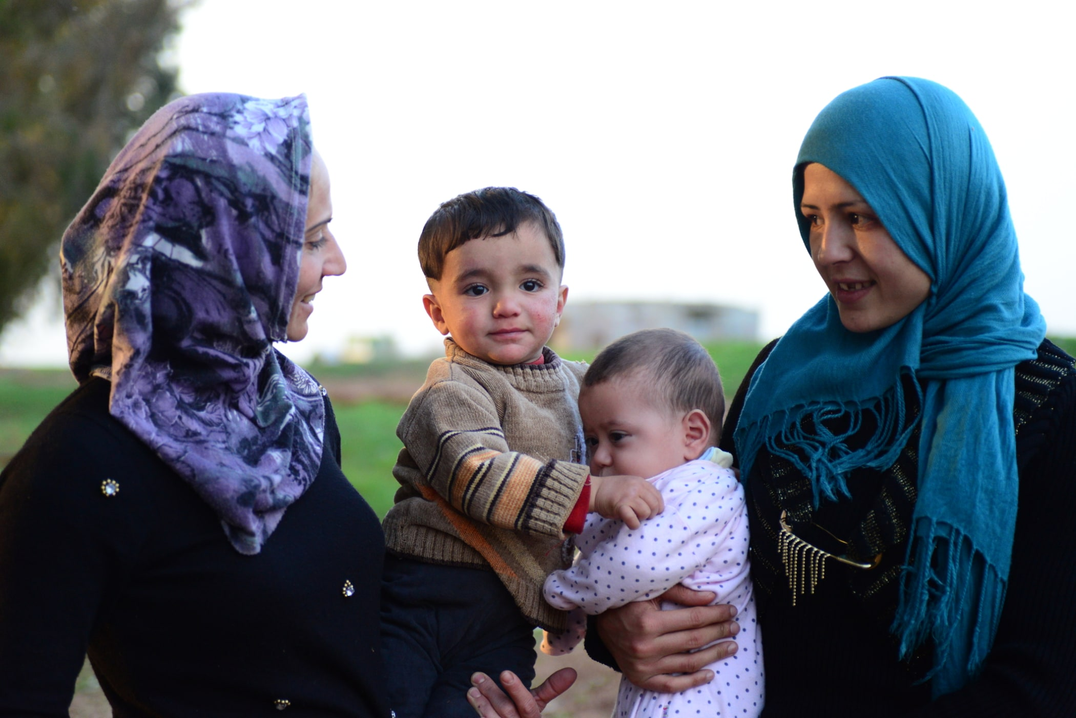 Syrian refugee mothers proudly hold their young children, Turkey.