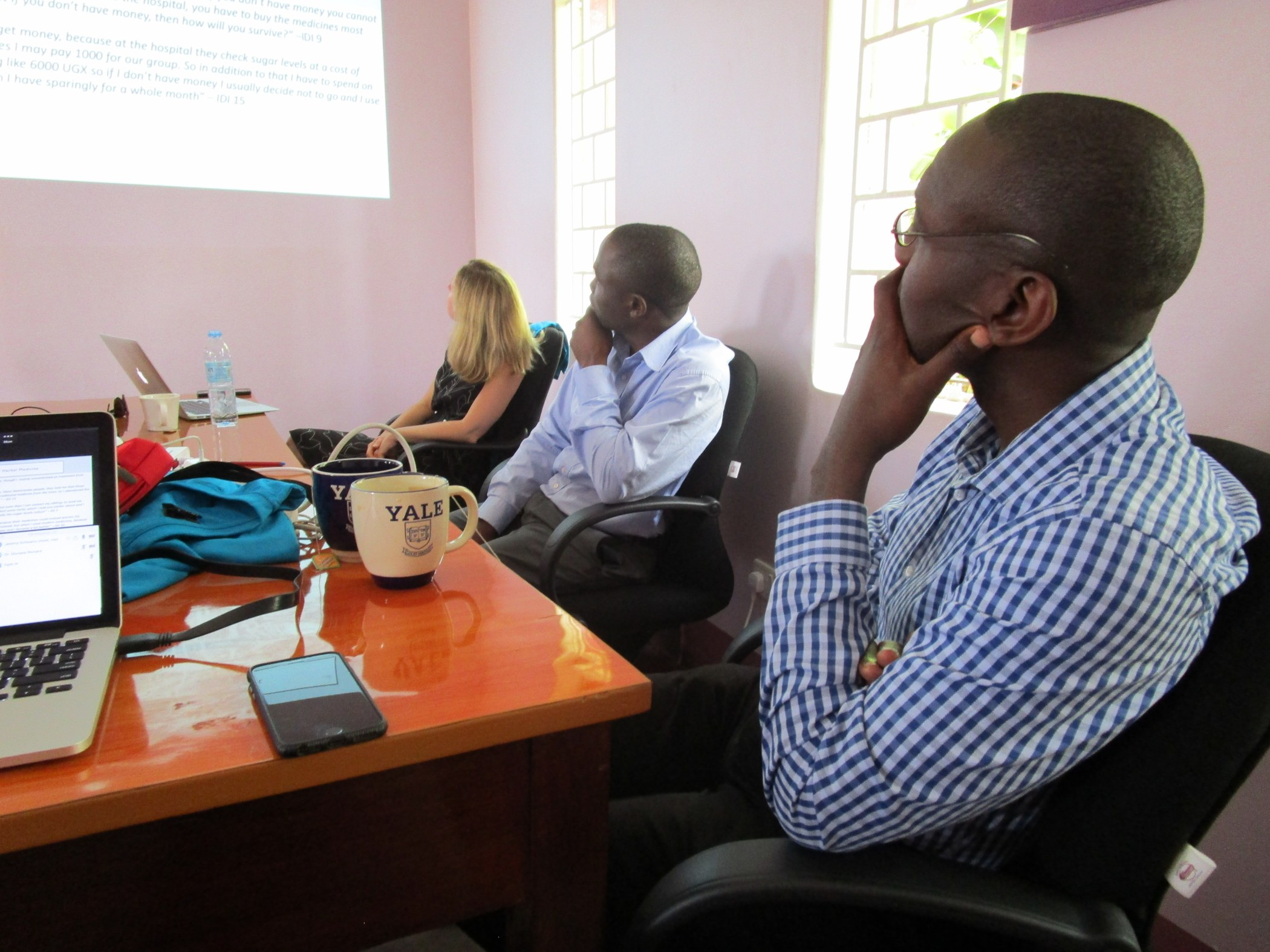 Drs. Robert Kalyesubula (right), Isaac Ssinabulya (middle) and NGN collaborator Mari Armstrong Hough, PhD (left) listen to a presentation of data by NGN fellow Andrew Tusubira, MPH.