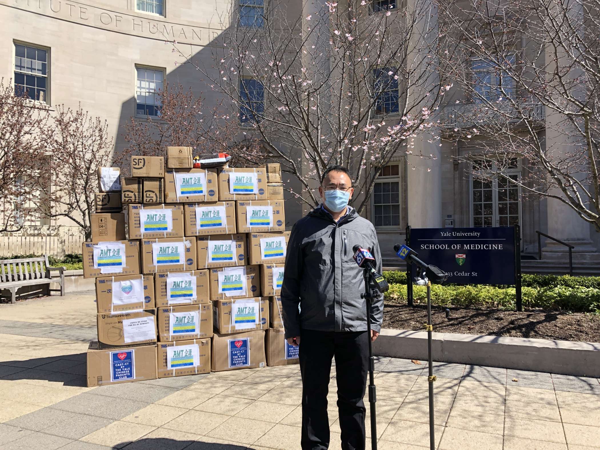 Jiankan Guo, PhD, stands in front of the large PPE donation he helped to obtain.