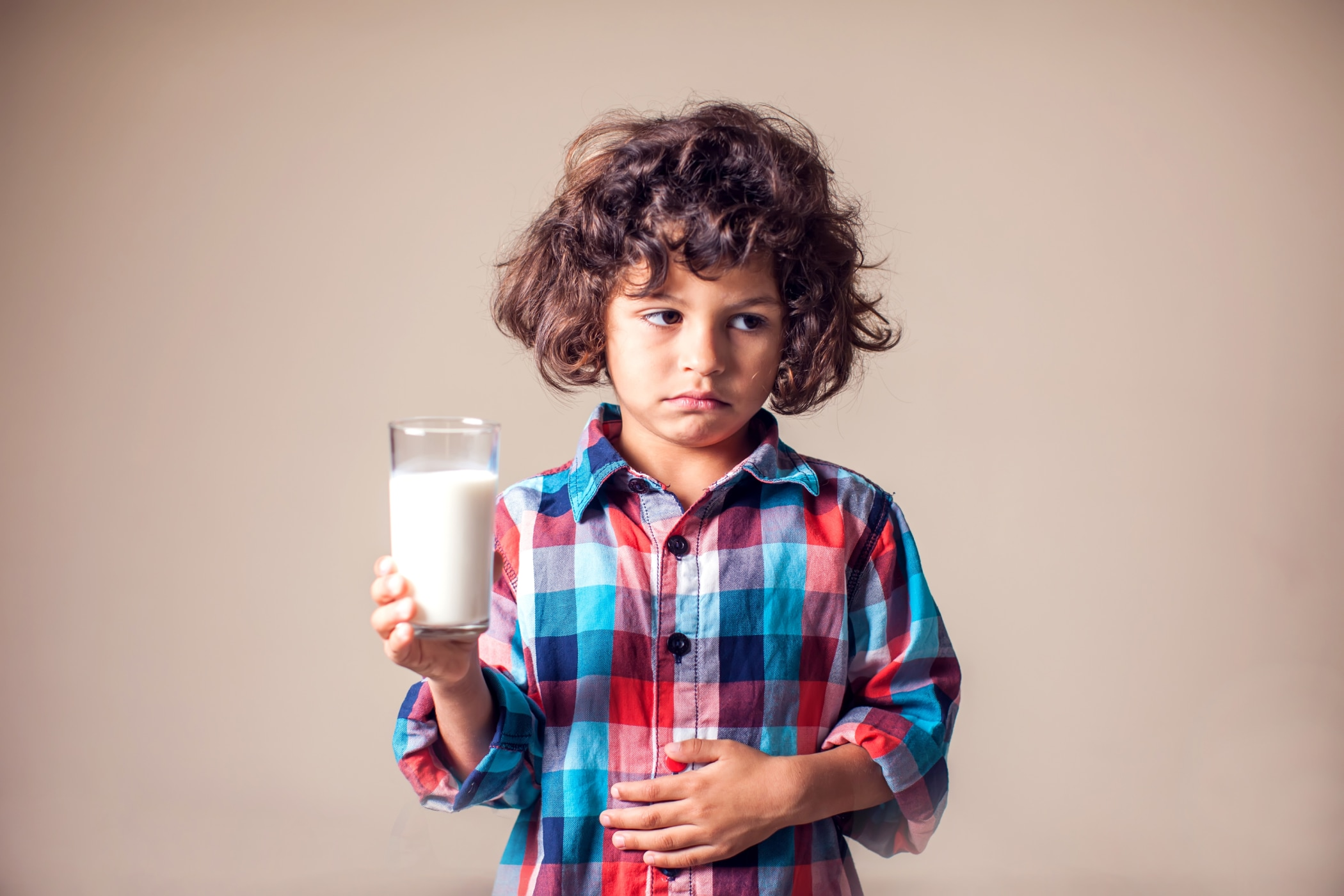 Boy with stomach pain holding a glass of milk