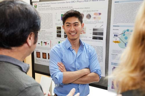 student at poster on student research day 2018