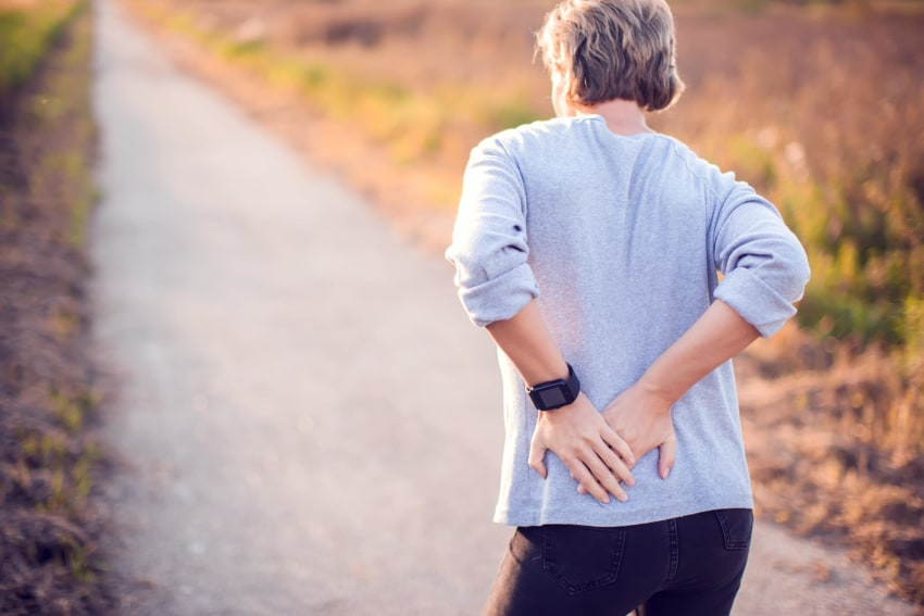 Woman walking outside and holding her lower back in pain