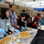 Volunteers hand food to a mother at World Refugee Day.