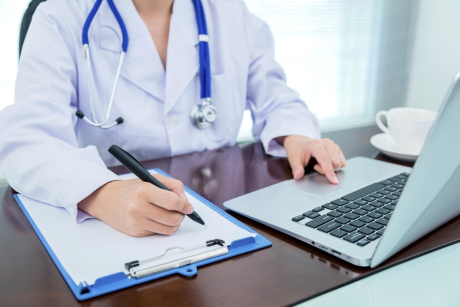Doctor at desk taking notes and using laptop