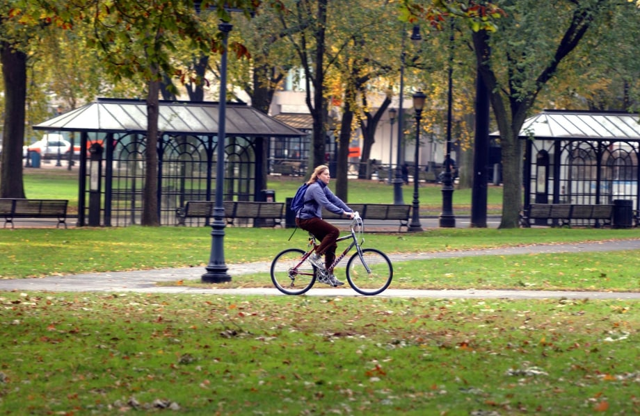 Woman riding a bicycle across the New Haven Green.