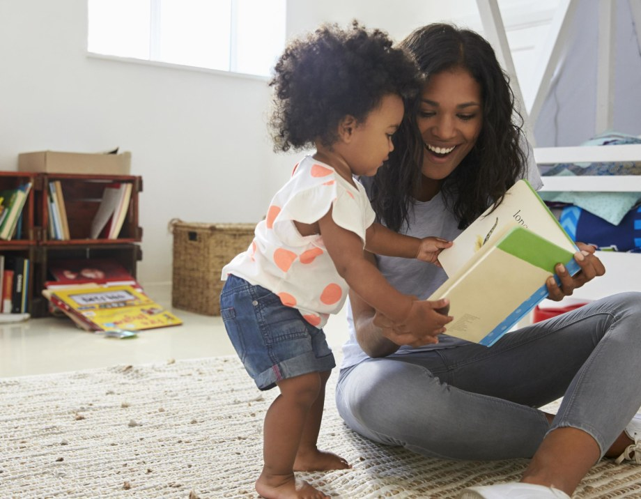 A photograph shows a woman sitting on the floor, smiling and holding a children's book. Her daughter, a toddler, stands next to her and looks at the book while holding open the pages.